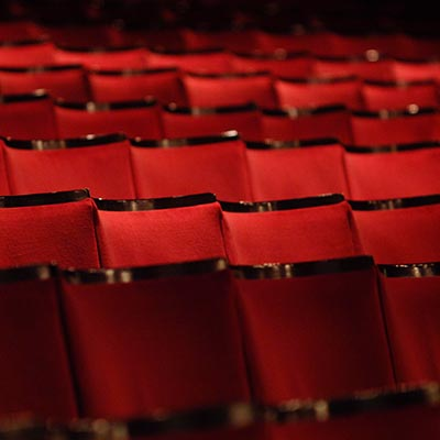 A row of red empty seats in the auditorium at the Alhambra Theatre