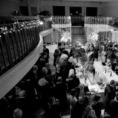 Black and white photograph of customers enjoying an evening in Winter Gardens with main staircase and balcony decorated with lights