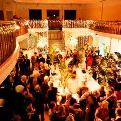 Customers enjoying an evening in Winter Gardens with main staircase and balcony decorated with lights