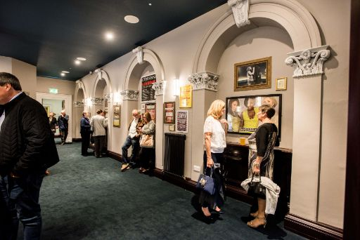 Customers talking in first floor bar at St George's Hall where there are framed posters of previous music acts on the walls