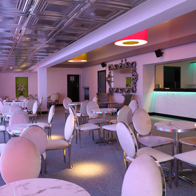 The bar area at The Studio with white marble tables, plush white chairs and illuminated pink ceiling light