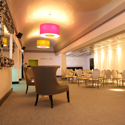View of the bar area from the back of the room showing pink and lime green illuminated ceiling lights