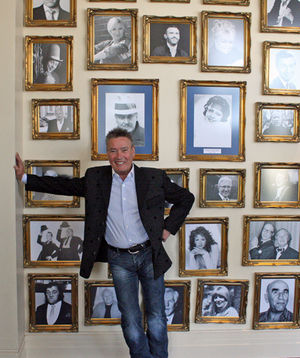 Comedian Billy Pearce standing in front of the wall of fame at the Alhambra Theatre, which features framed pictures of past performers