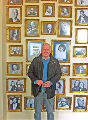 Actor Duncan Preston standing in front of the wall of fame at the Alhambra Theatre, which features framed pictures of past performers